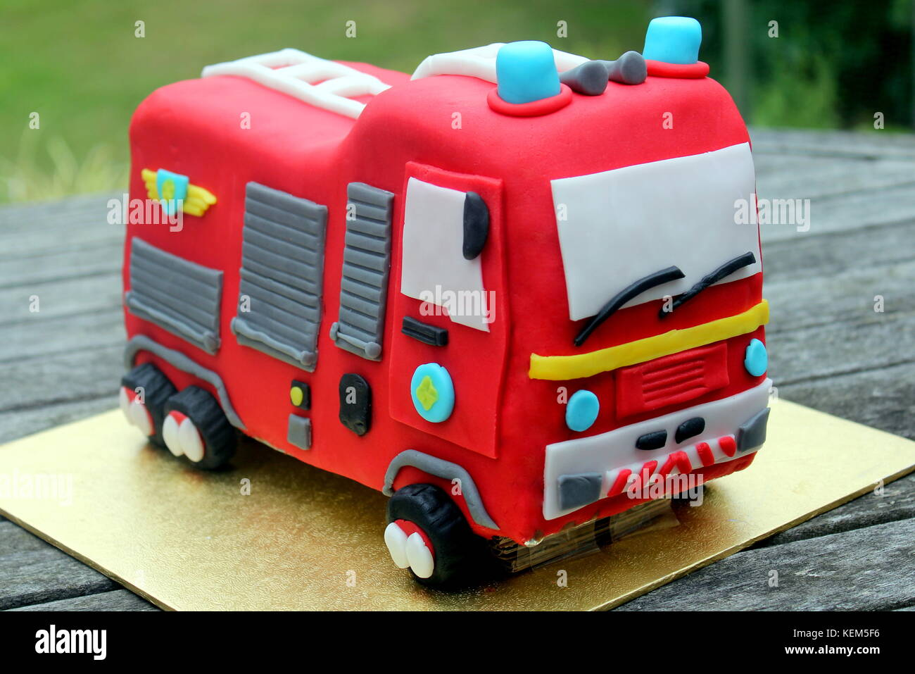Childs homemade red fire engine birthday celebration cake on a