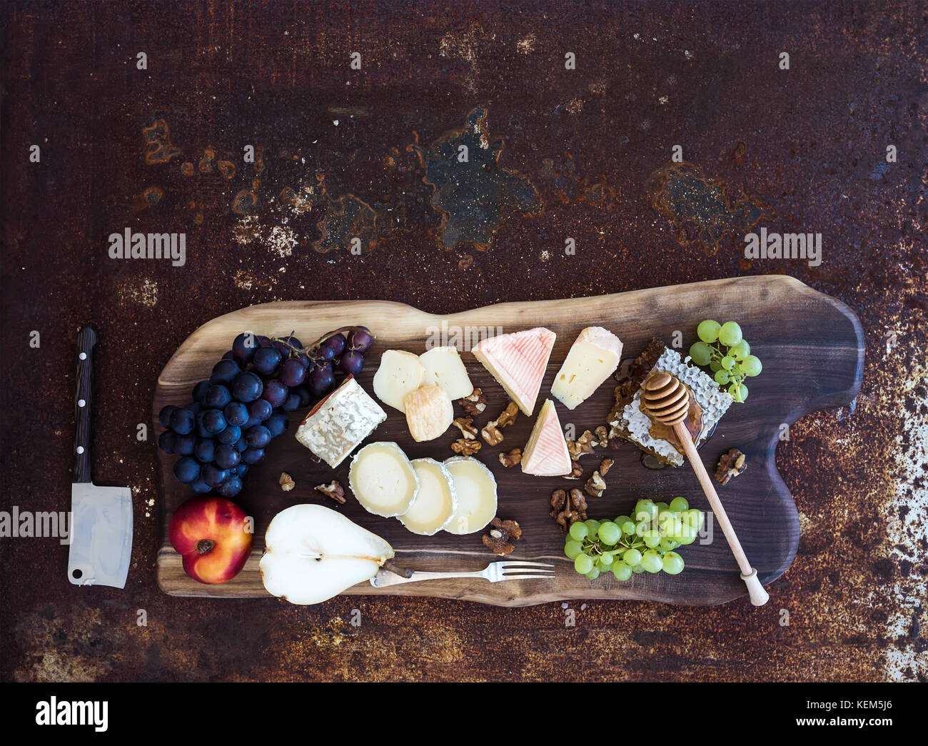 Wine appetizers set: French cheese selection, honeycomb, grapes, peach and walnuts on rustic wooden board over dark - Stock Image