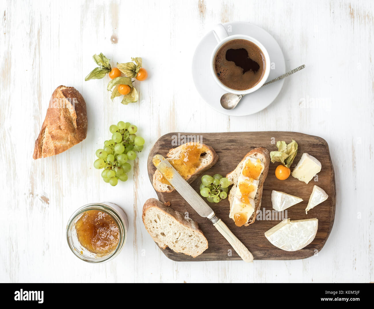 Breakfast set. Brie cheese and fig jam sandwiches with fresh grapes, ground cherries. Cup of coffee. Top view - Stock Image