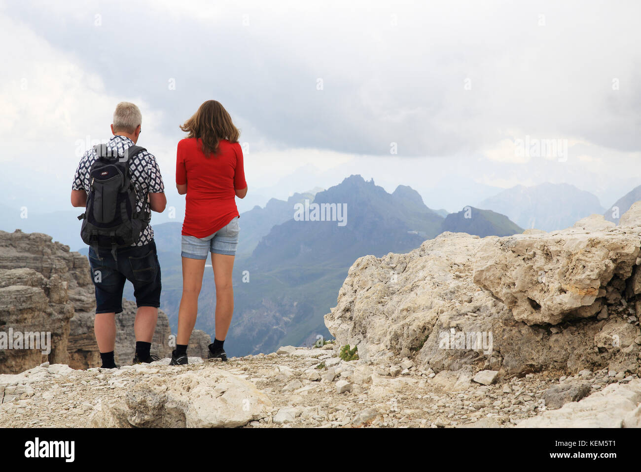 Couple walking at the Pordoi Pass, in Canazei, in the Dolomites, in the Province of Trento, north Italy - Stock Image