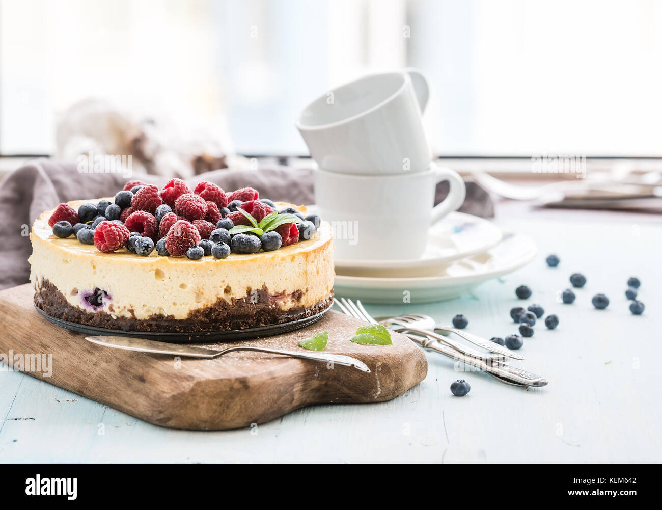 Cheesecake with fresh raspberries and blueberries on a wooden serving board, plates, cups, kitchen napkin, silverware - Stock Image