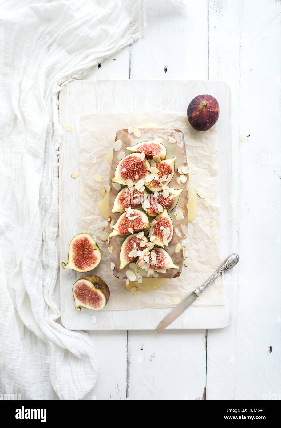 Loaf cake with figs, almond and white chocolate on wooden serving board over light background - Stock Image