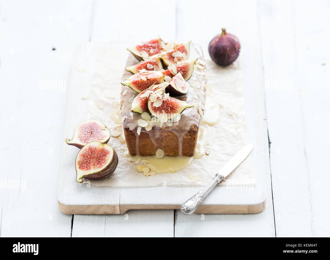 Loaf cake with figs, almond and white chocolate on wooden serving board over grunge background, selective focus. - Stock Image