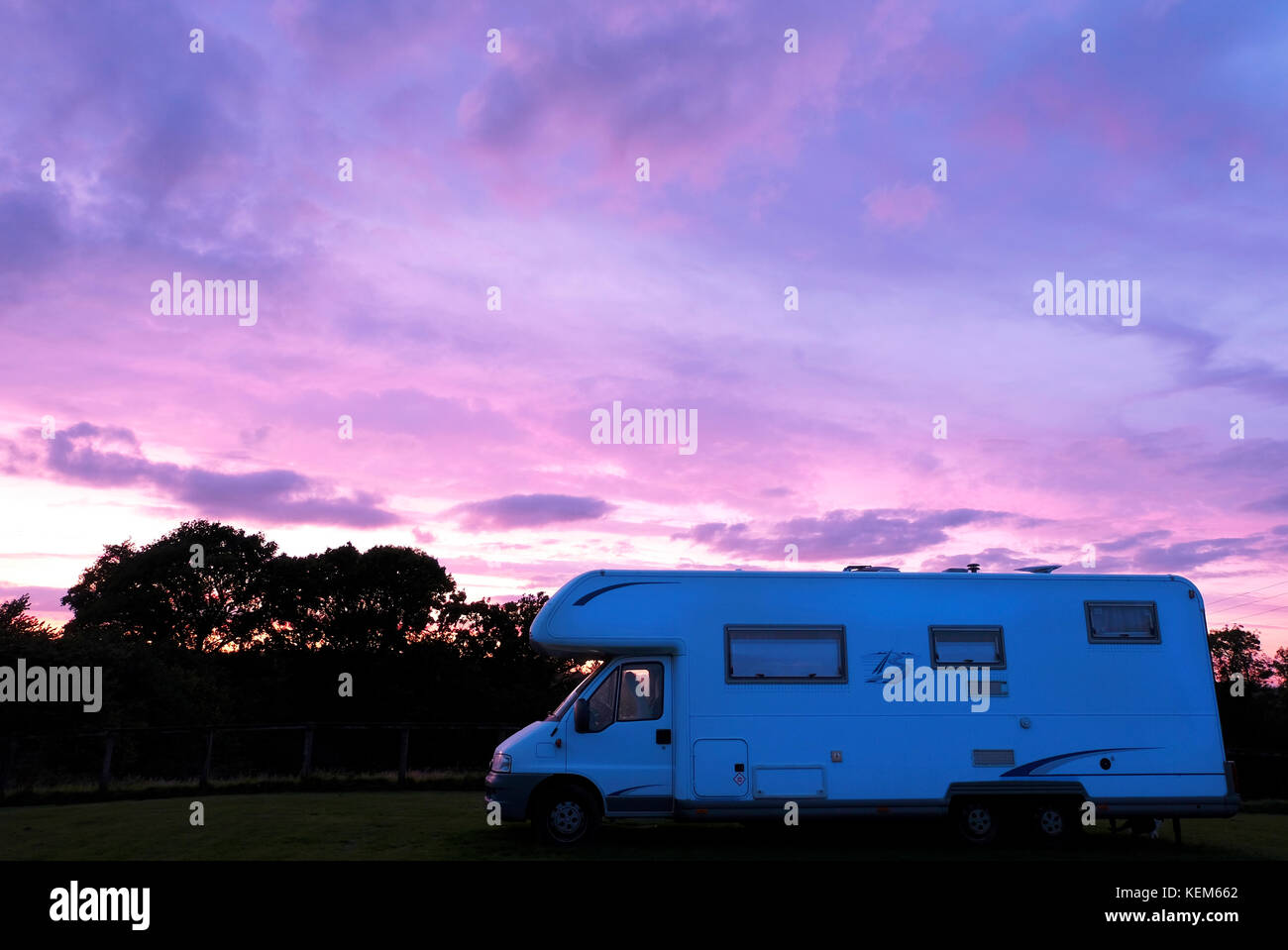 Large Motorhome parked in field at sunset in Sussex, UK - Stock Image