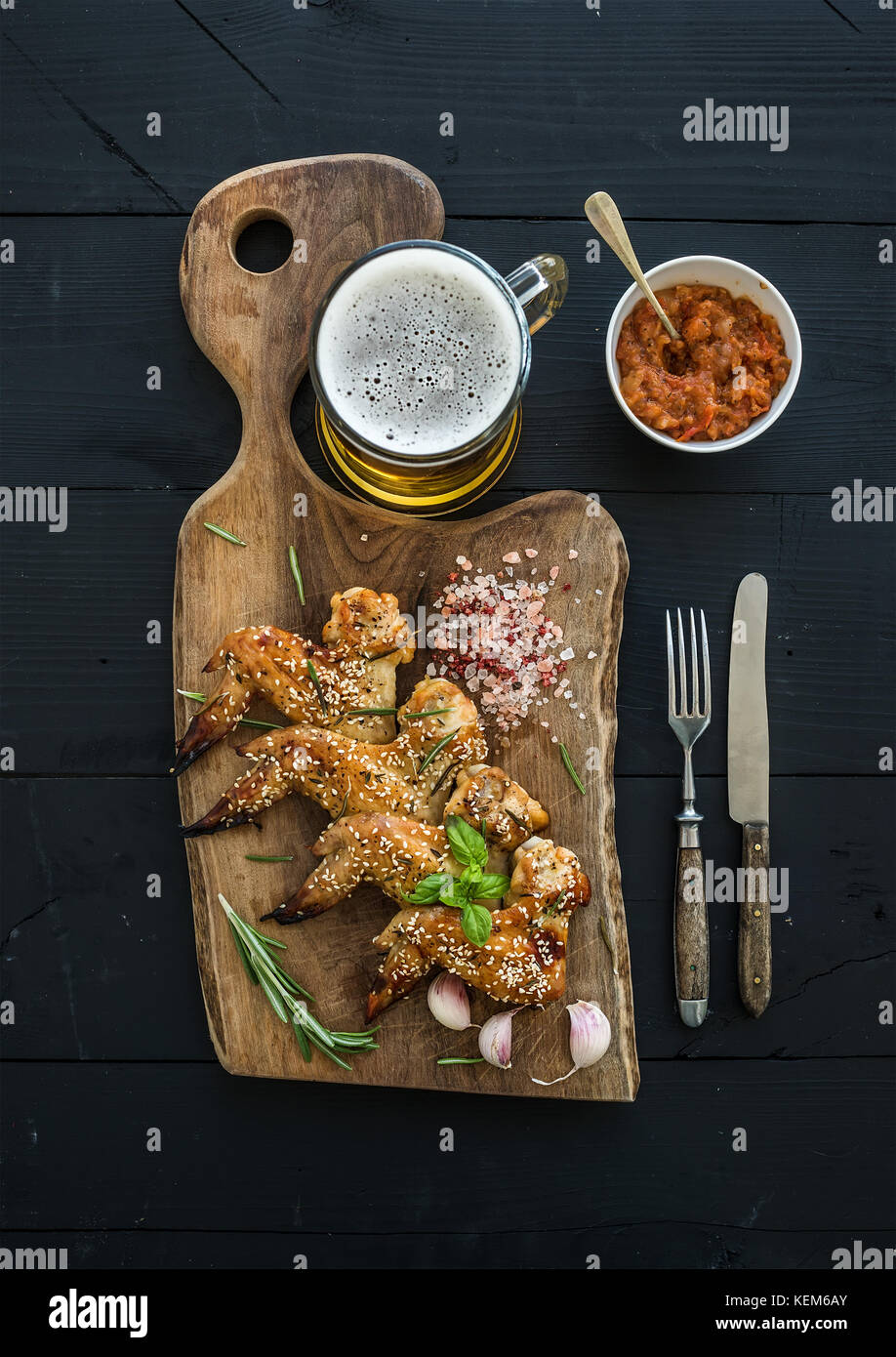 Fried chicken wings on rustic serving board, spicy tomato sauce, herbs and mug of light beer over black wooden backdrop - Stock Image