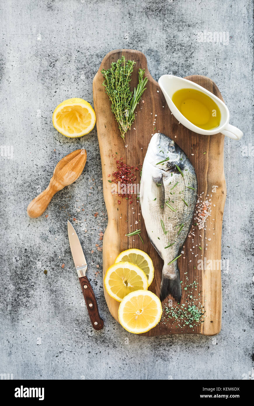 Fresh uncooked dorado or sea bream fish with lemon, herbs, oil and spices on rustic wooden board over grunge backdrop - Stock Image