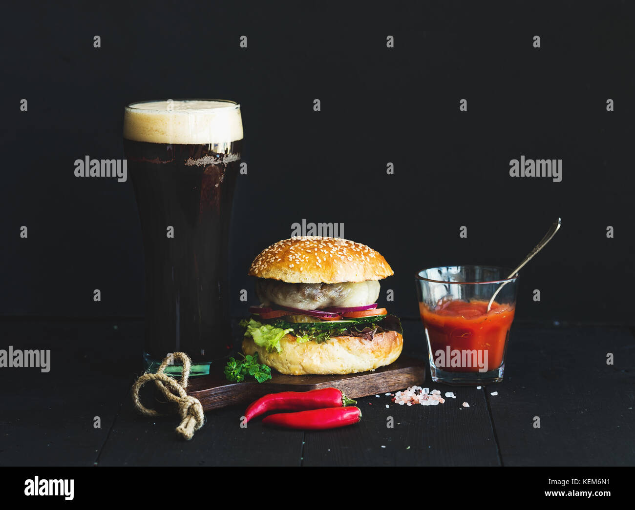 Fresh homemade burger on wooden serving board with spicy tomato sauce, sea salt, herbs and glass of dark beer over Stock Photo