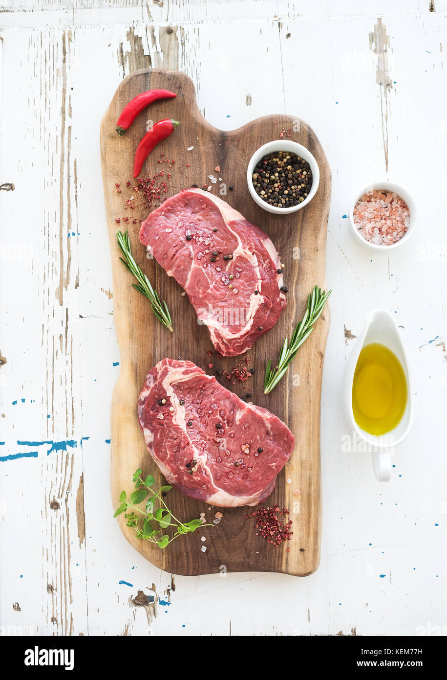 Raw fresh meat Ribeye steak entrecote and seasonings on cutting board over white wooden background. Stock Photo