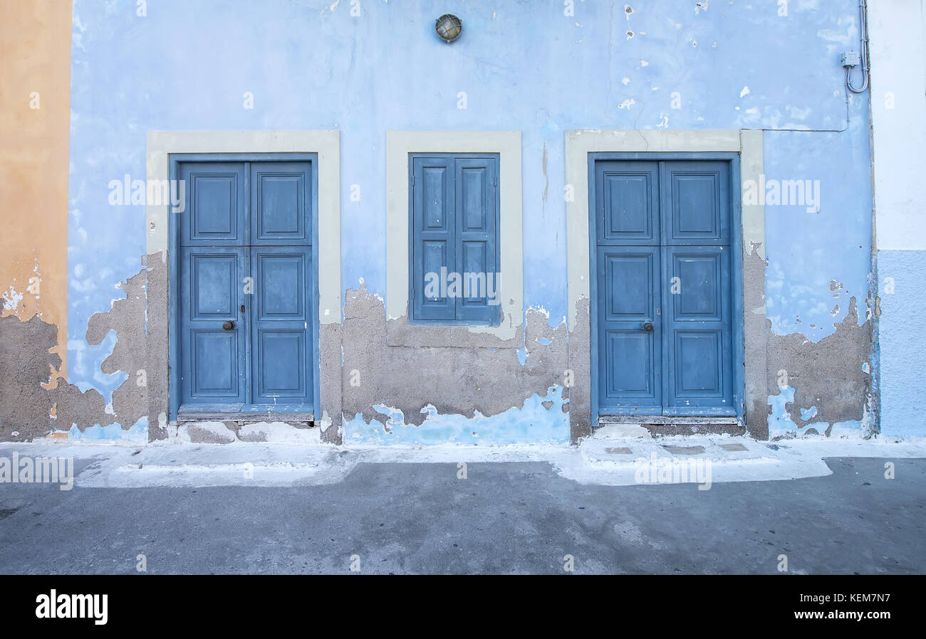 Mediterranean style exterior. Blue wooden doors and window shutters ...