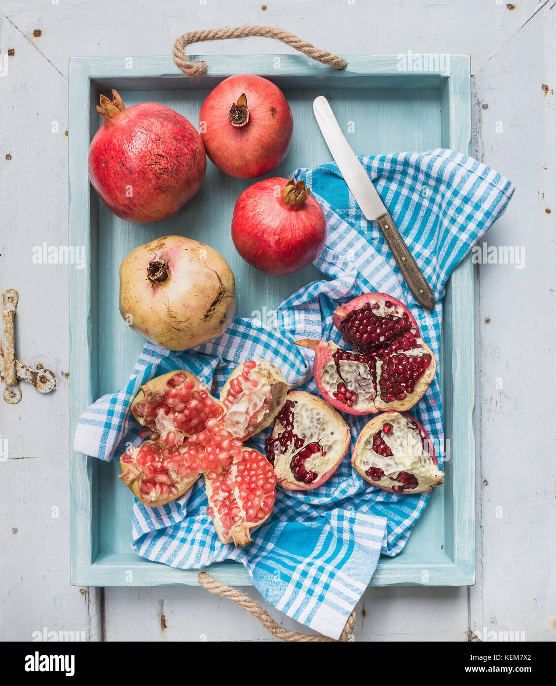 Red and white pomegranates with knife on kitchen towel in blue tray over light painted wooden backdrop Stock Photo