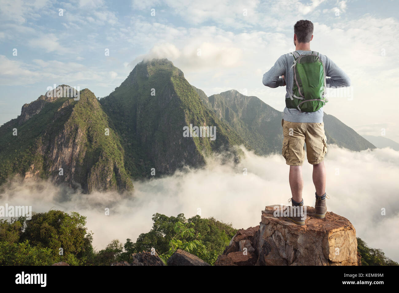 Hiker in front of a tropical mountain panorama - Stock Image