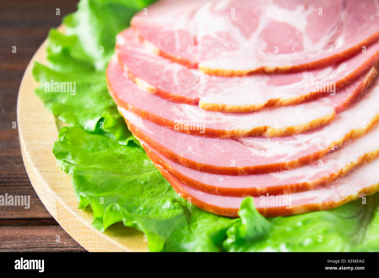 Sliced ham with fresh green lettuce leaves on a round cutting board. Meat products on a brown wooden table. - Stock Image