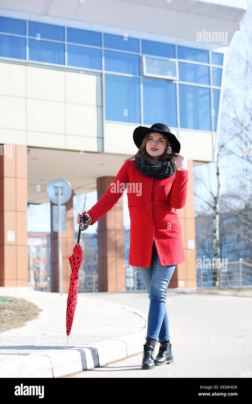 Cute businesswoman in a red coat against a background of glass Stock Photo