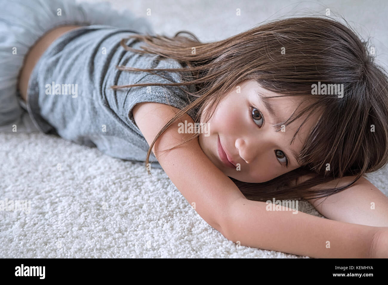 Five year old girl laying on the carpet in her room - Stock Image