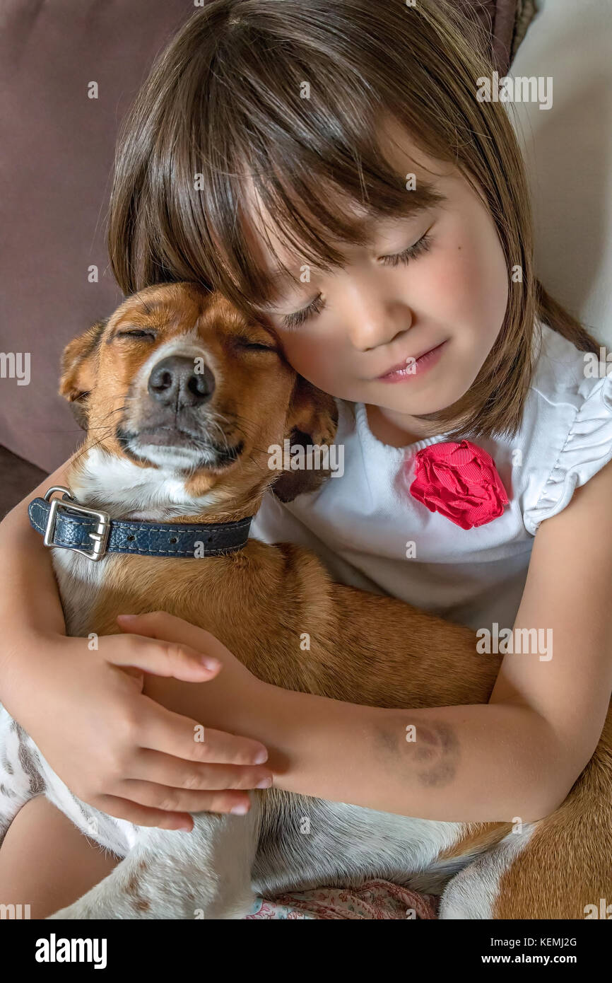 A toddler girl and her pet with closed eyes - Stock Image