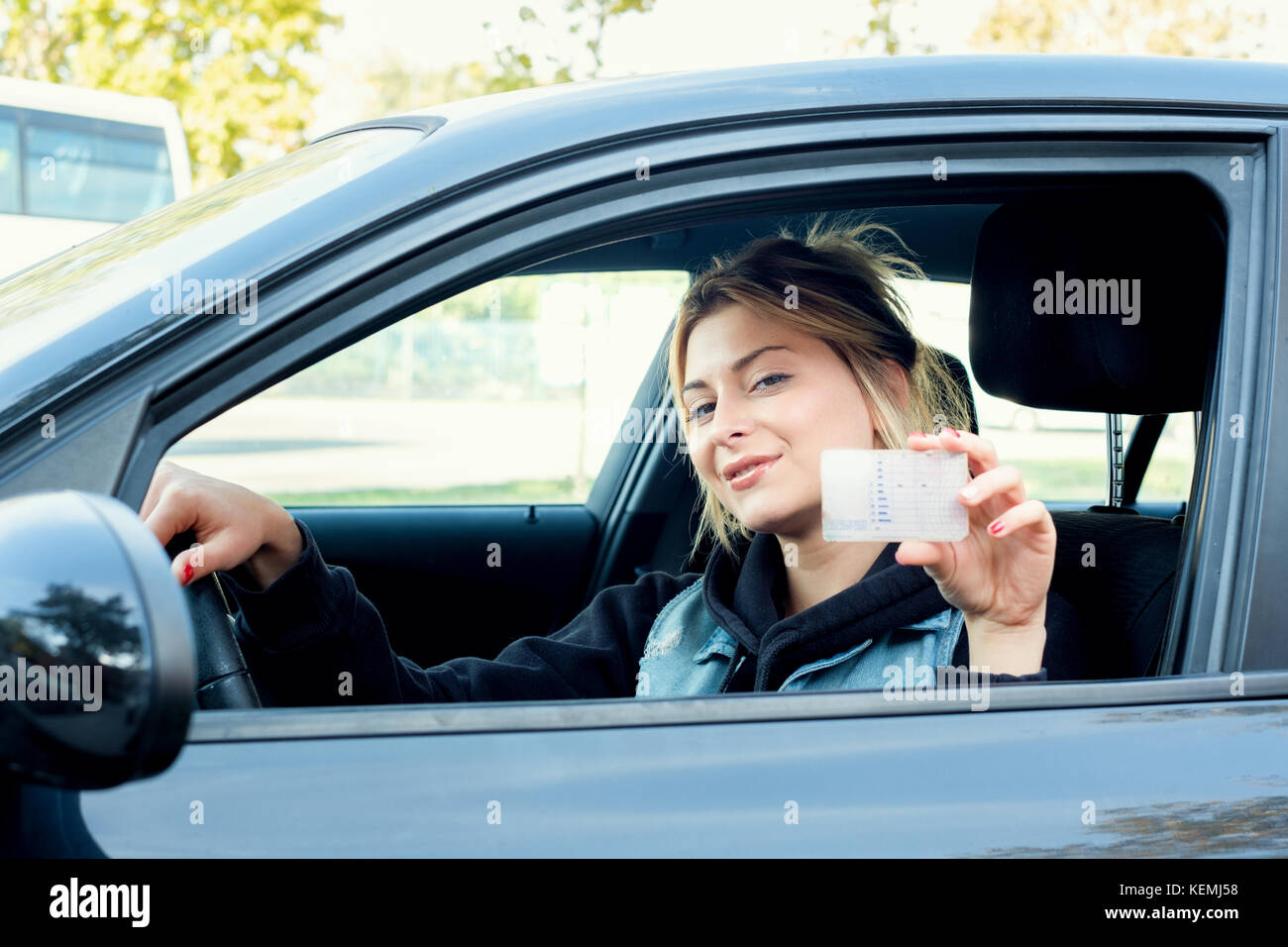 Young girl holding her new driving license seated in the car Stock Photo
