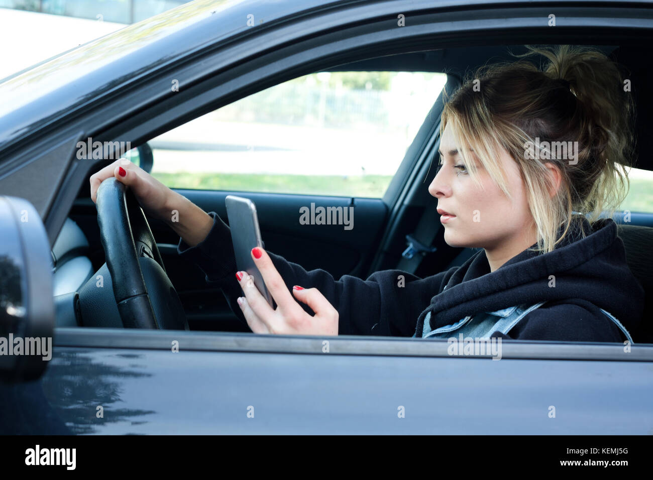 Girl driving car and texting on her smart phone - Stock Image