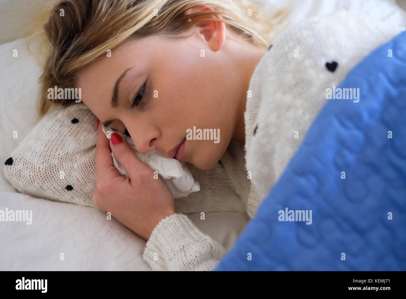 Young girl is crying and lying in the bed - Stock Image