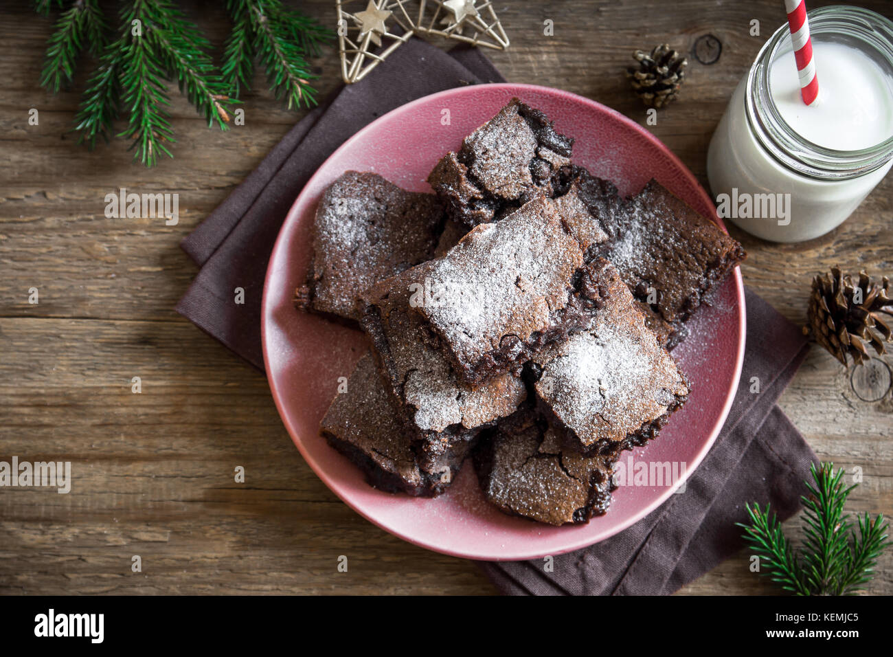 Brownies for Christmas and winter holidays. Homemade chocolate fudge brownies with milk on rustic wooden table. - Stock Image
