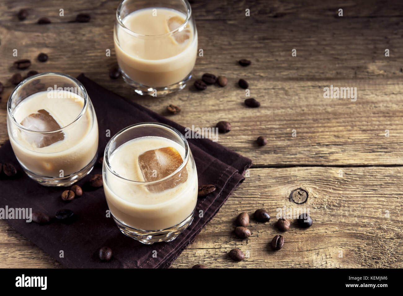 Irish cream coffee liqueur with ice, chocolate candies and coffee beans over rustic wooden background - homemade Stock Photo
