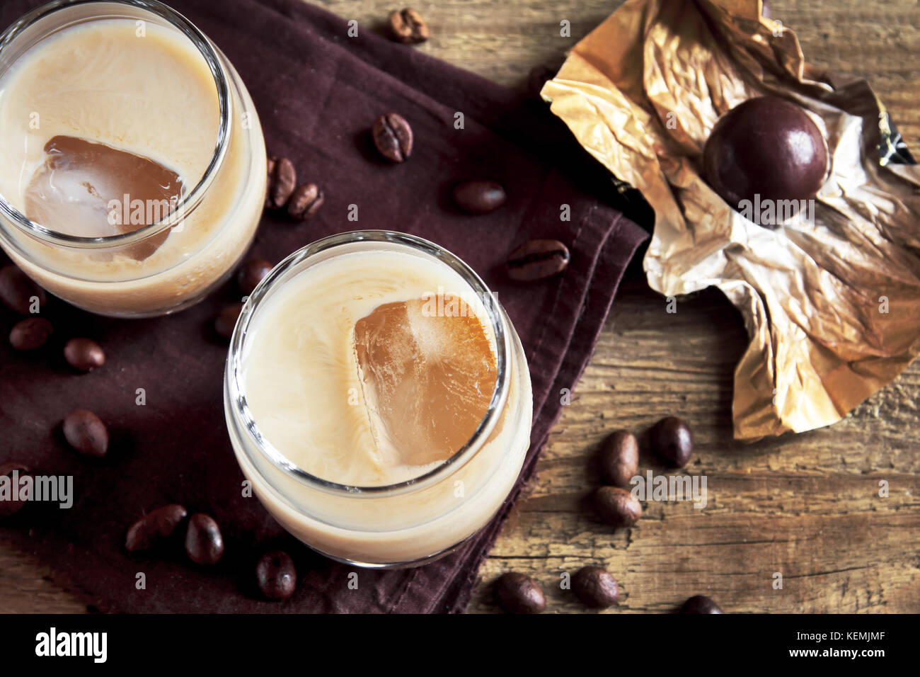 Irish cream coffee liqueur with ice, chocolate candies and coffee beans over rustic wooden background - homemade - Stock Image