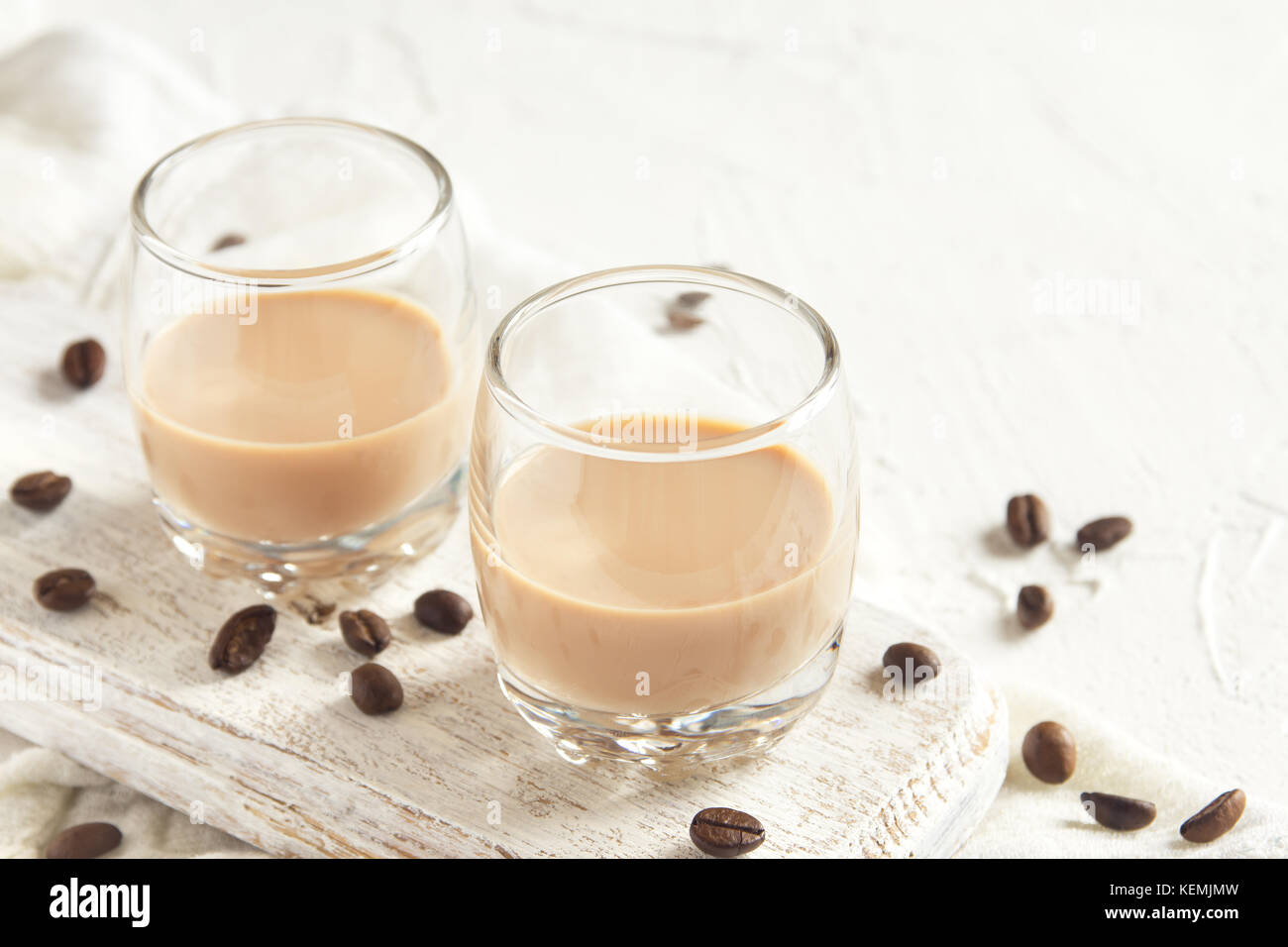 Irish cream coffee liqueur and coffee beans over white wooden background - homemade festive alcoholic drink - Stock Image