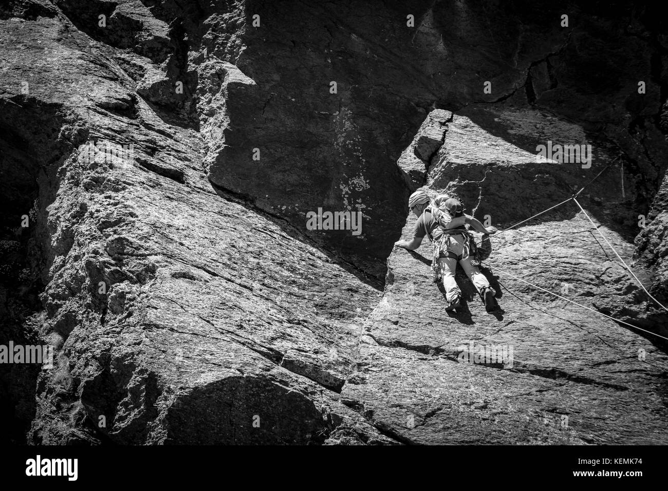 From below panoramic view of man climbing high on mountain - Stock Image