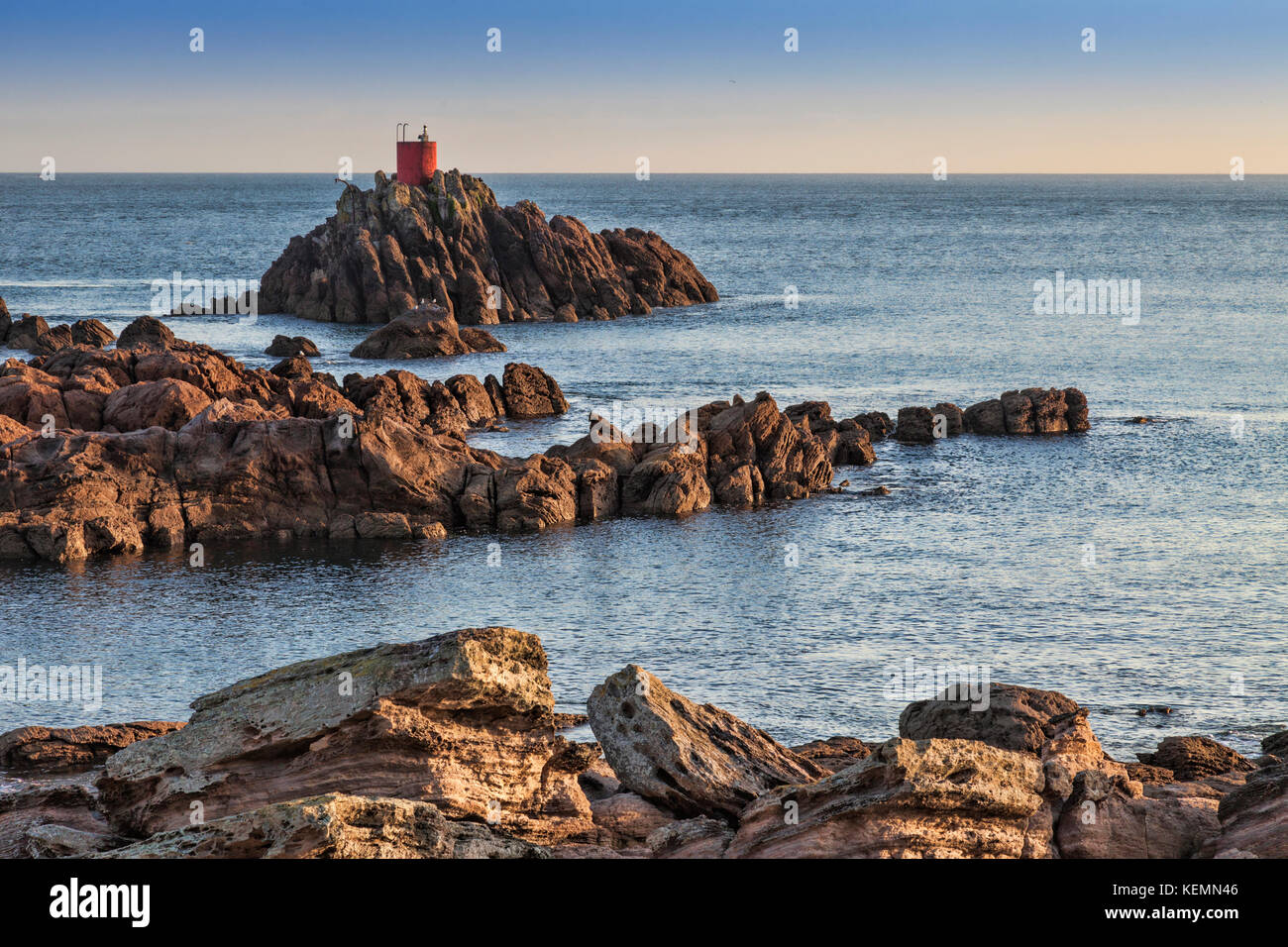 Offshore rocks and lighthouse on the entrance channel to the Port of Tauranga, Bay of Plenty, New Zealand. - Stock Image