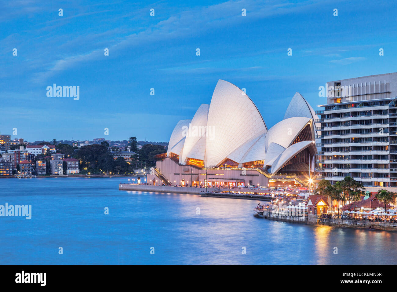 Sydney Opera House illuminated at twilight, the building beside it is known as The Toaster. - Stock Image