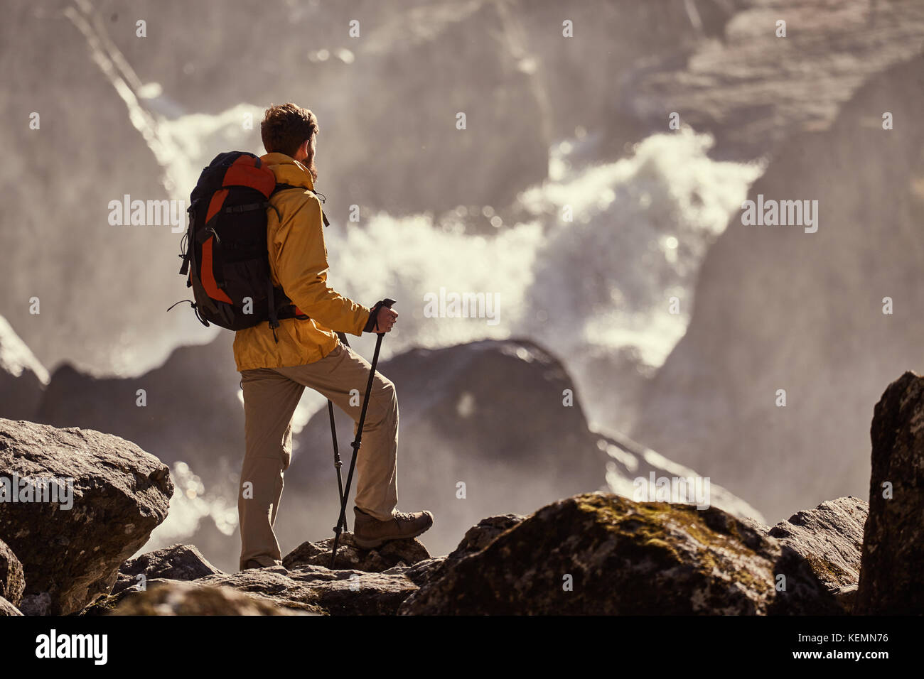 Hiker hiking with backpack looking at waterfall - Stock Image