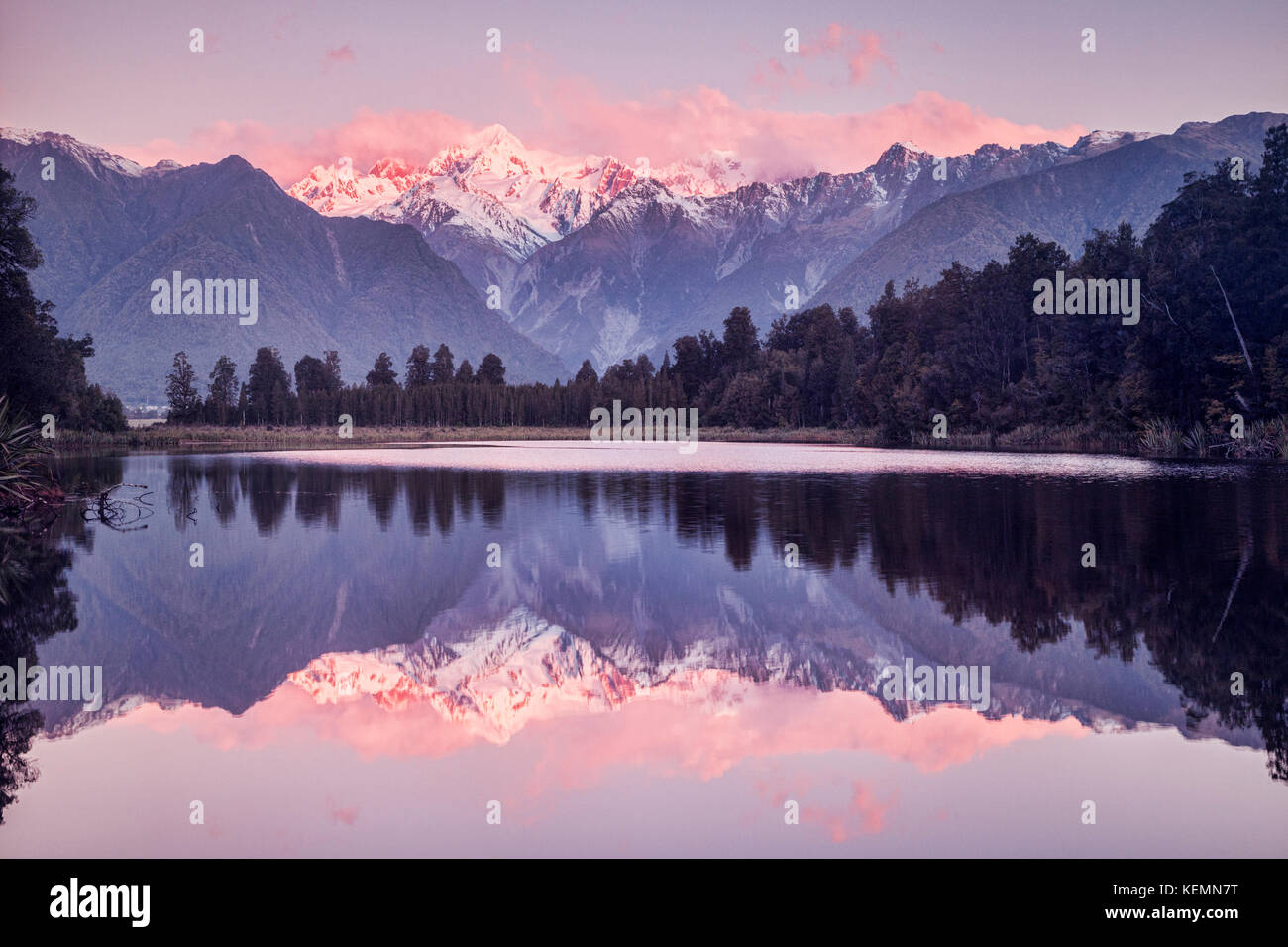 Lake Matheson at sunset with snow covered Mount Tasman and, in the cloud, Aoraki-Mount Cook, New Zealand's highest - Stock Image