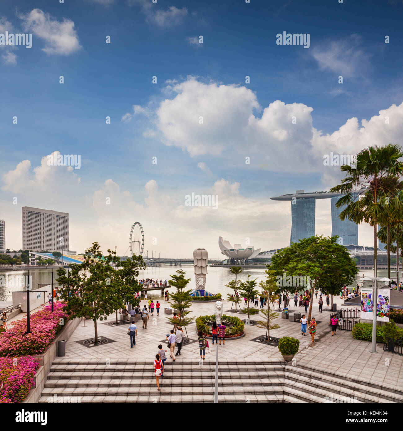 Tourists near the Merlion and looking out over some of the major tourist attractions of Singapore - the Marina Bay - Stock Image