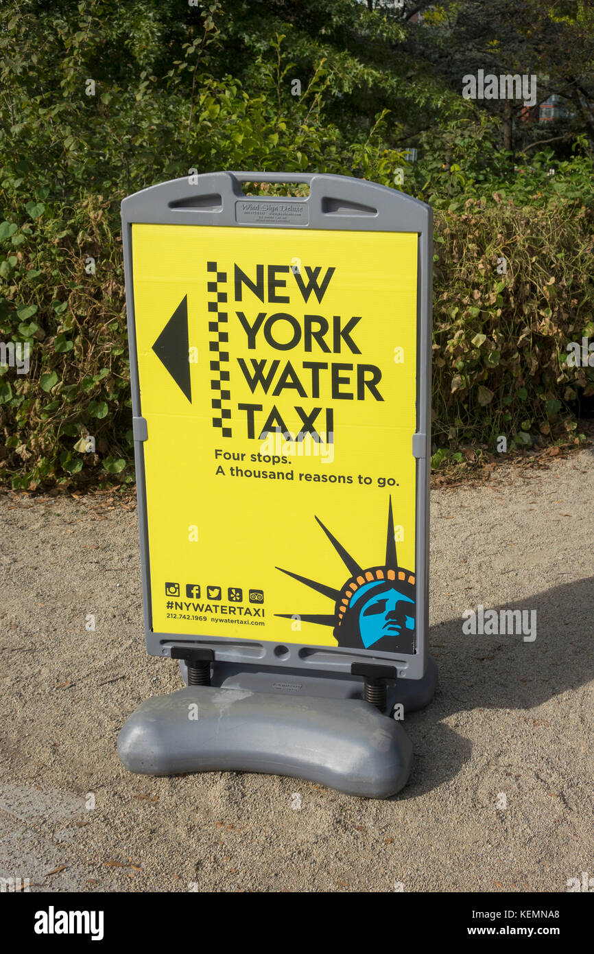A yellow sign in Battery Park pointing to a place to get a New York Water Taxi - Stock Image