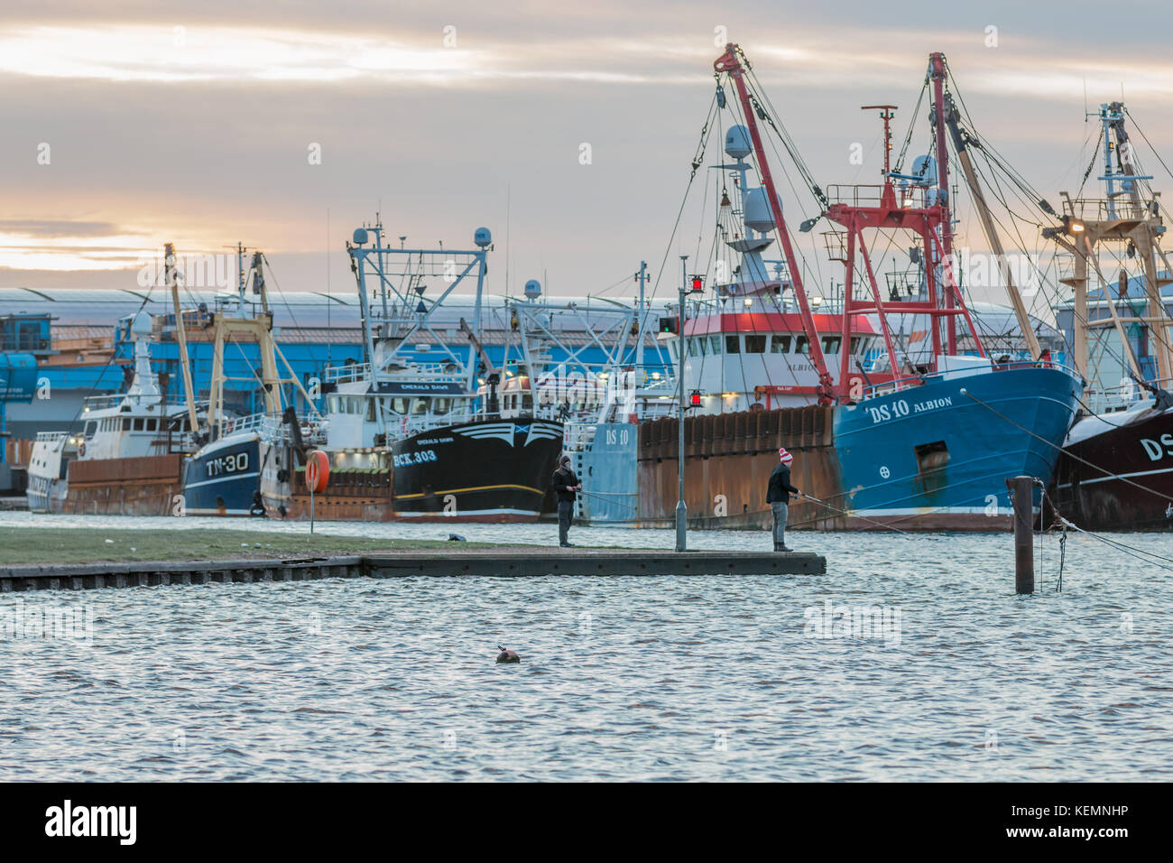 22nd October 2017; Shoreham Port, West Sussex, UK; two men fishing with rods within the port just after dawn. Fleet Stock Photo
