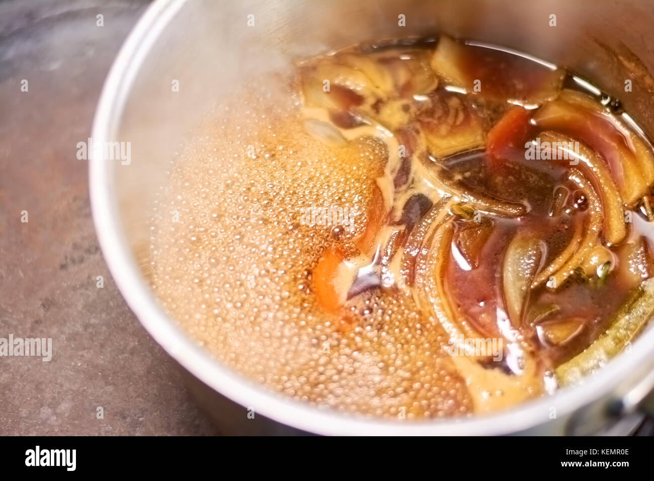 Flavor shank of lamb boiling in saucepan. Slow cooked leg of lamb with broth in casserole close up. Delicious food - Stock Image