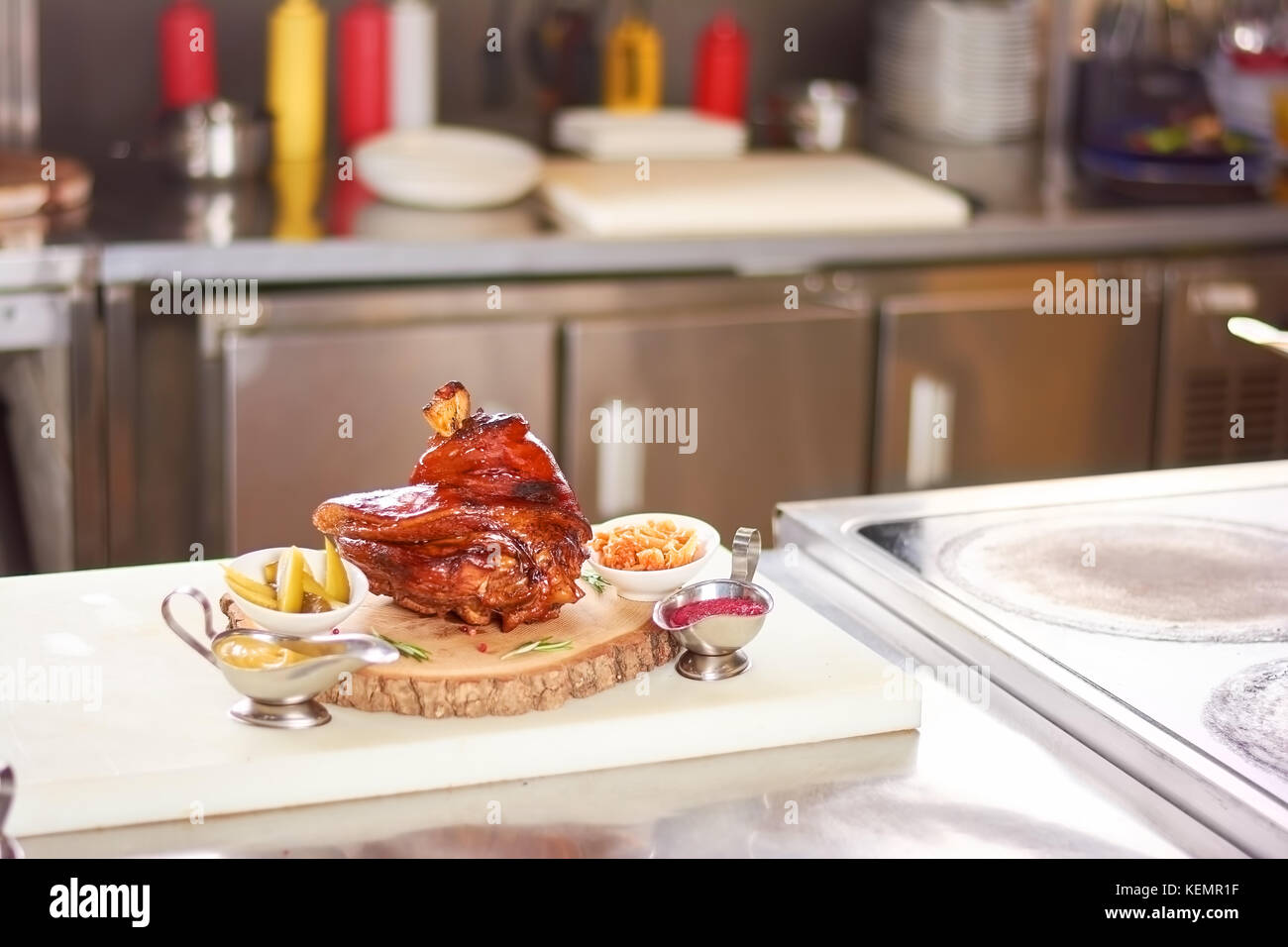 Delicious shank of lamb on narural wood. Large piece of roasted lamb leg served with sauces and spices. Fresh cooked - Stock Image