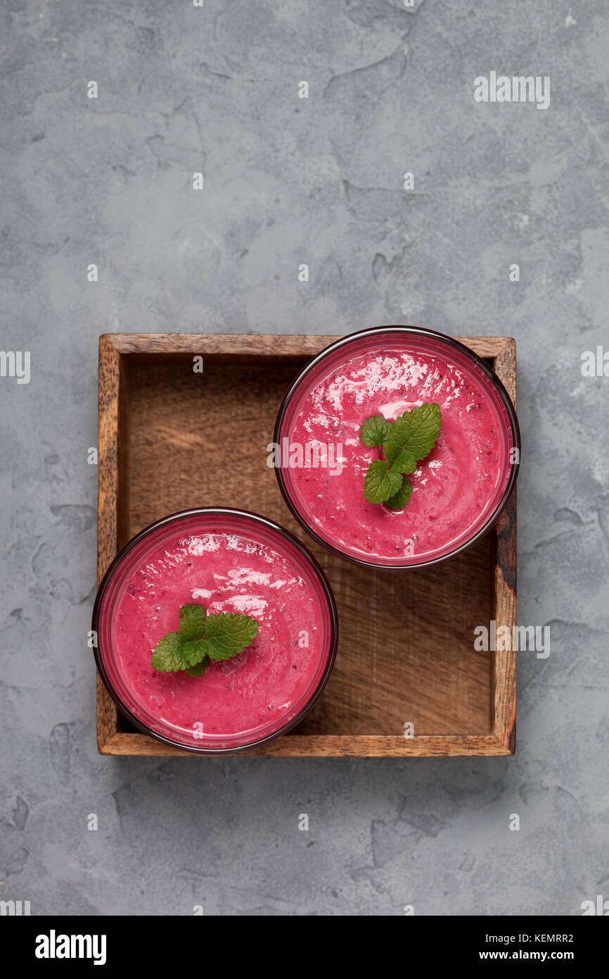 red berry fruit smoothies in glasses on a gray concrete background. view from above. copy space Stock Photo