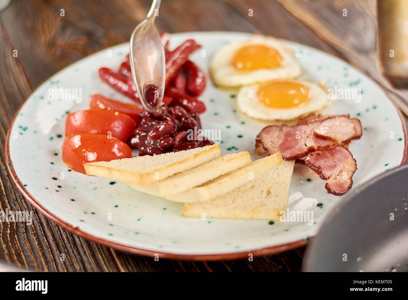 Full english breakfast on plate. Chef putting beans on plate with english breakfast. English breakfast in restaurant. - Stock Image