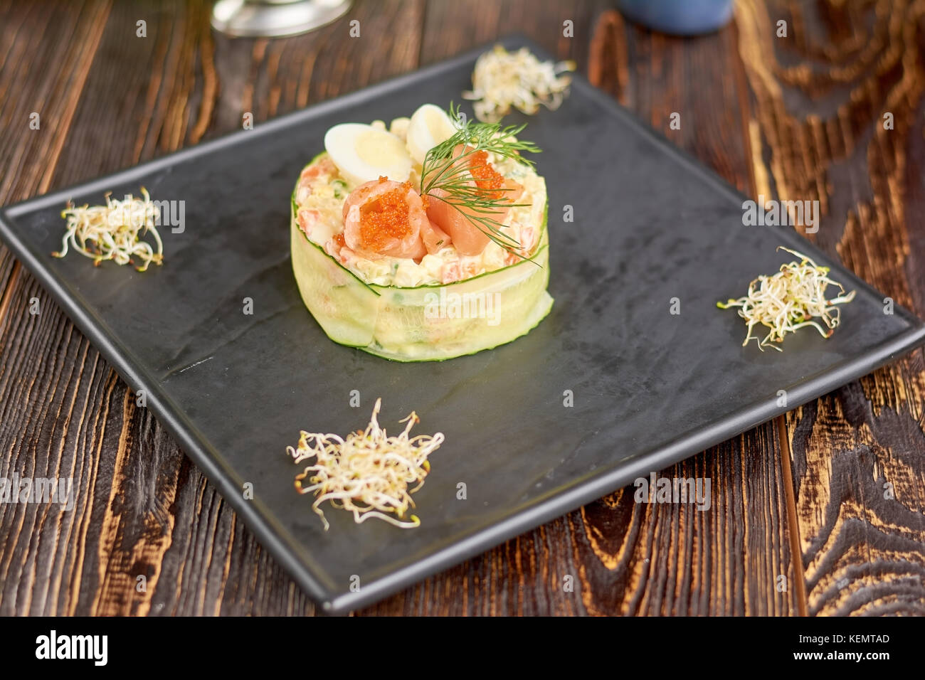 Olivier salad with salmon and tobiko caviar. Appetizing olivier salad on plate in restaurant. Delicious dinner on - Stock Image