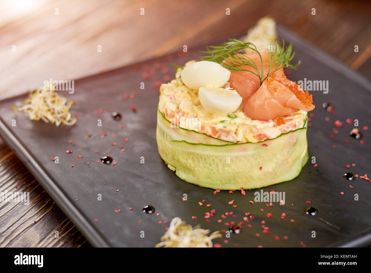 Delicious olivier with salmon, eggs and caviar. Traditional russian salad olivier with salmon, eggs, tobiko caviar, - Stock Image