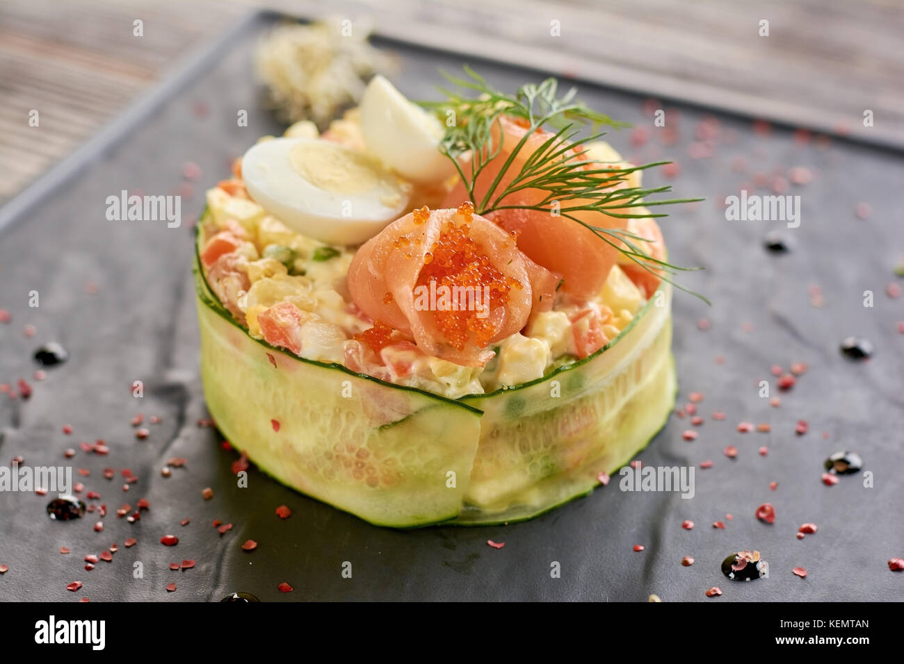 Olivier salad with salmon and tobiko caviar. Tasty olivier salad served with salmon, tobiko caviar, dill and eggs. - Stock Image