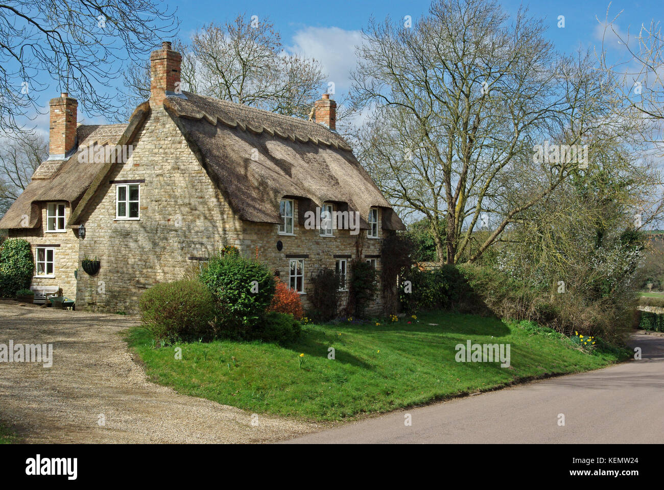 Detached house, with chimneys and a thatched roof, on the outskirts of the village of Harringworth, Northamptonshire, Stock Photo