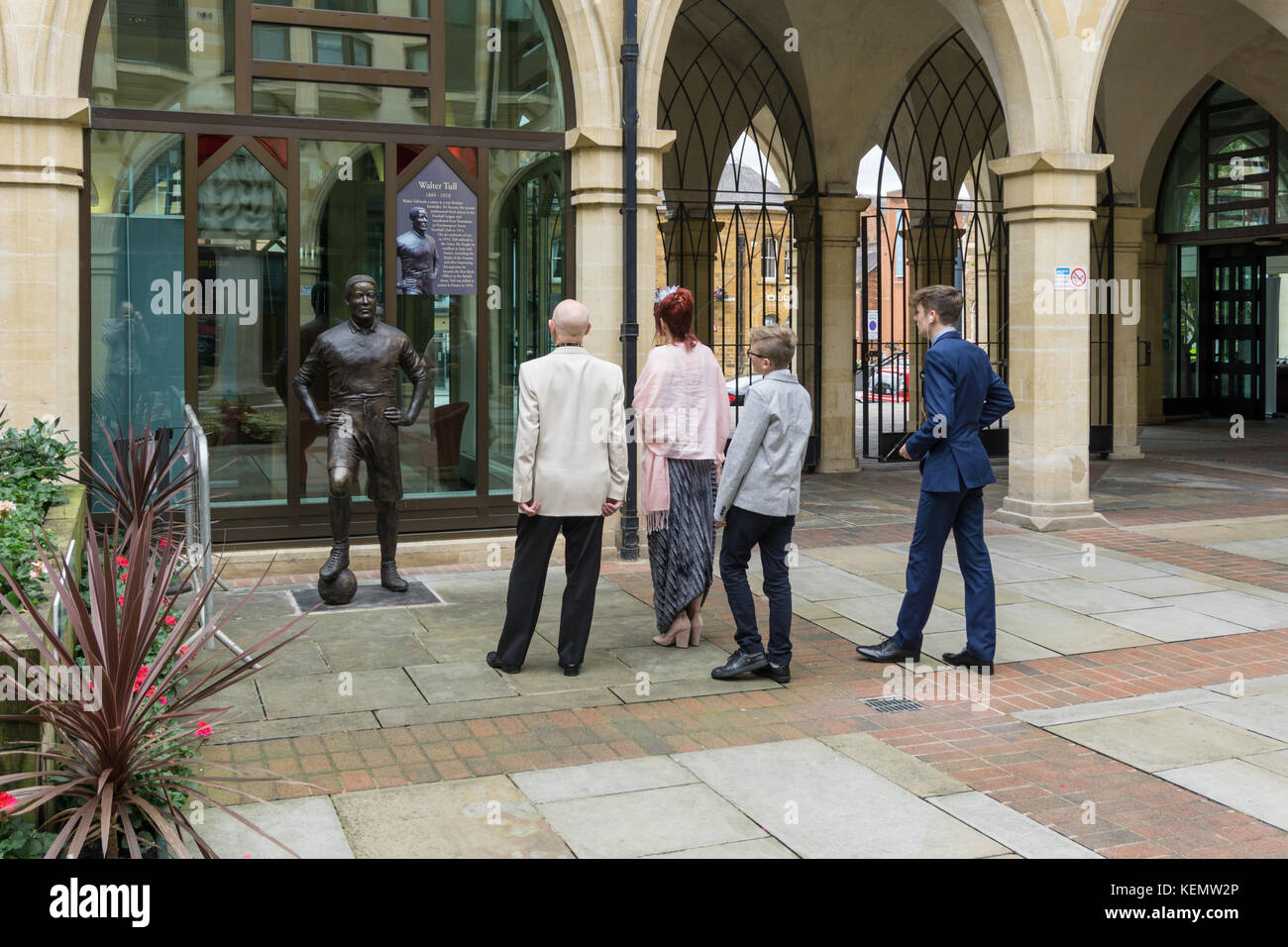 Four visitors viewing a statue of Walter Tull, footballer and war hero, in the courtyard of the Guildhall, Northampton, - Stock Image