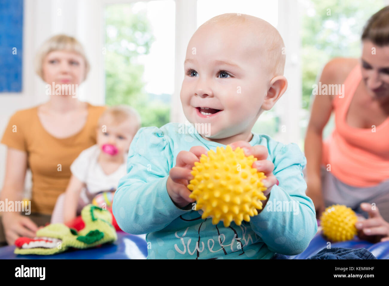 Babies with pacifier in toddler group playing with toys - Stock Image