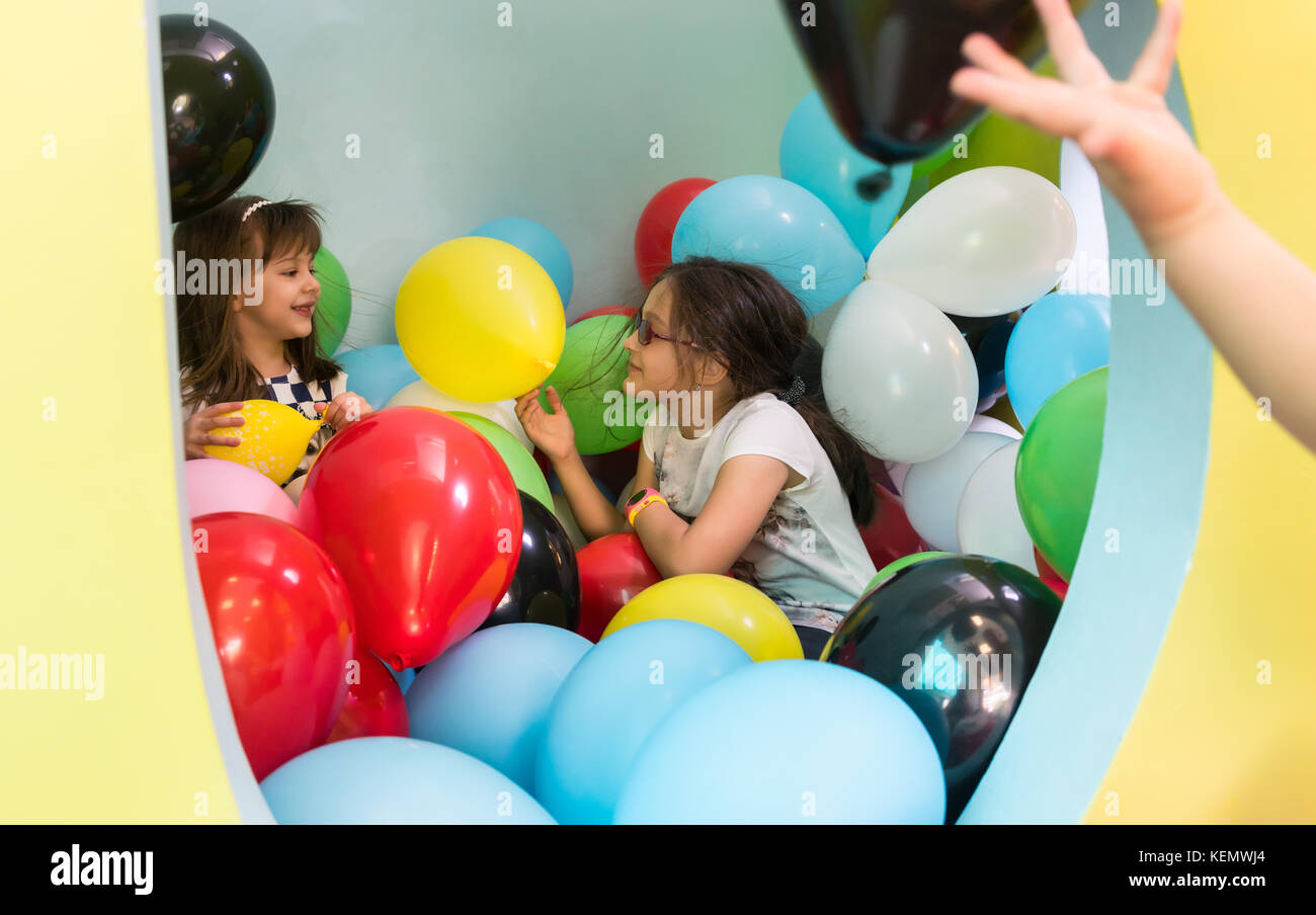 Two cute girls talking while playing with multicolored balloons  - Stock Image