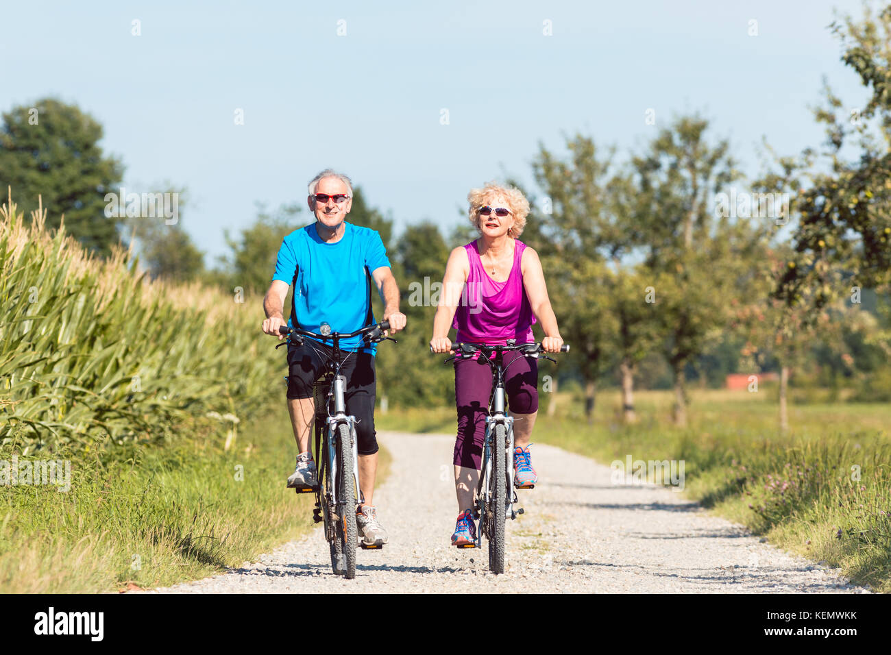 Active senior couple enjoying retirement while riding bicycles i - Stock Image