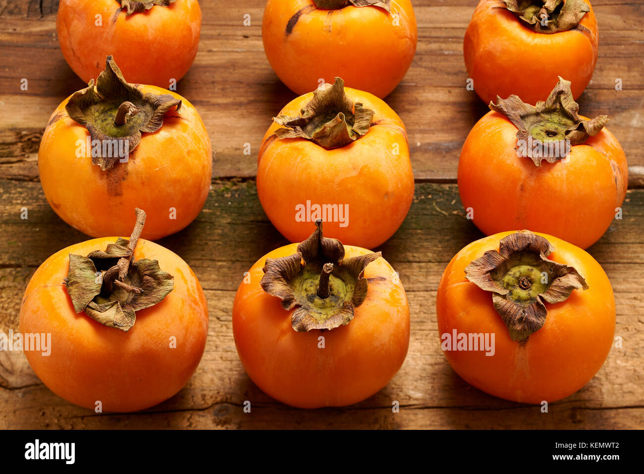 Colorful and fresh persimmons aligned on an old wooden table - Stock Image
