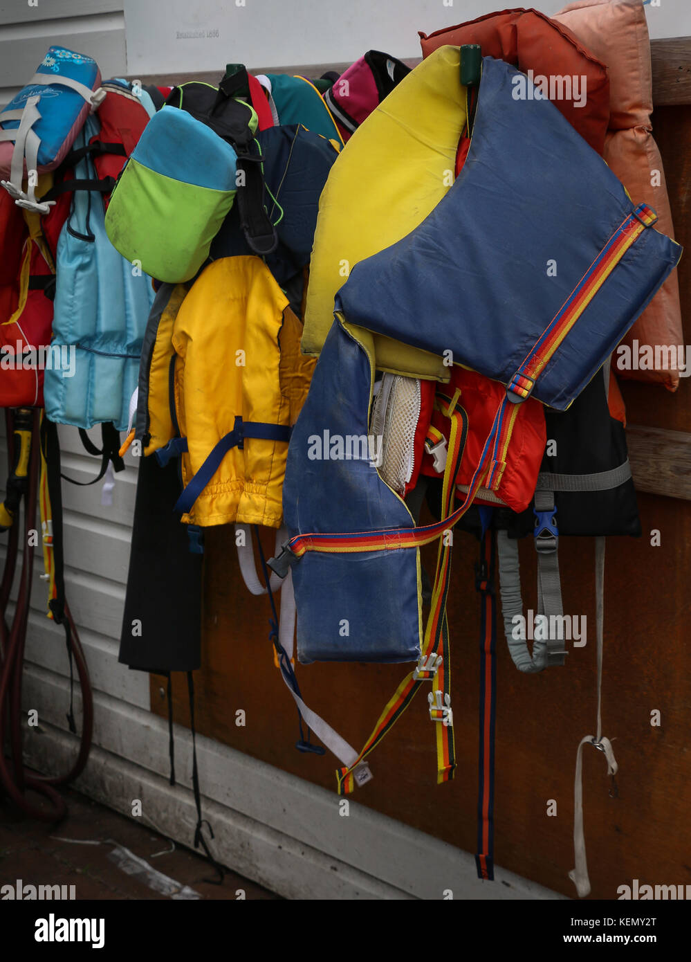 Many colorful life jackets of varying sizes hung  helter-skelter on knobs on an outside wall near a boat yard, the - Stock Image