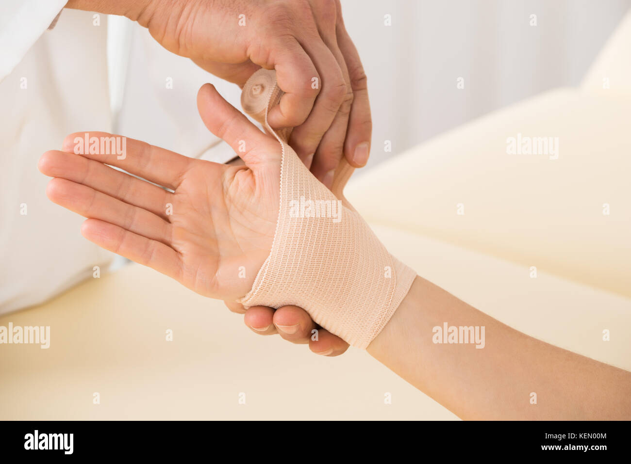 Close Up Of Doctor Hand Wrapping Elastic Bandage To Patient Stock