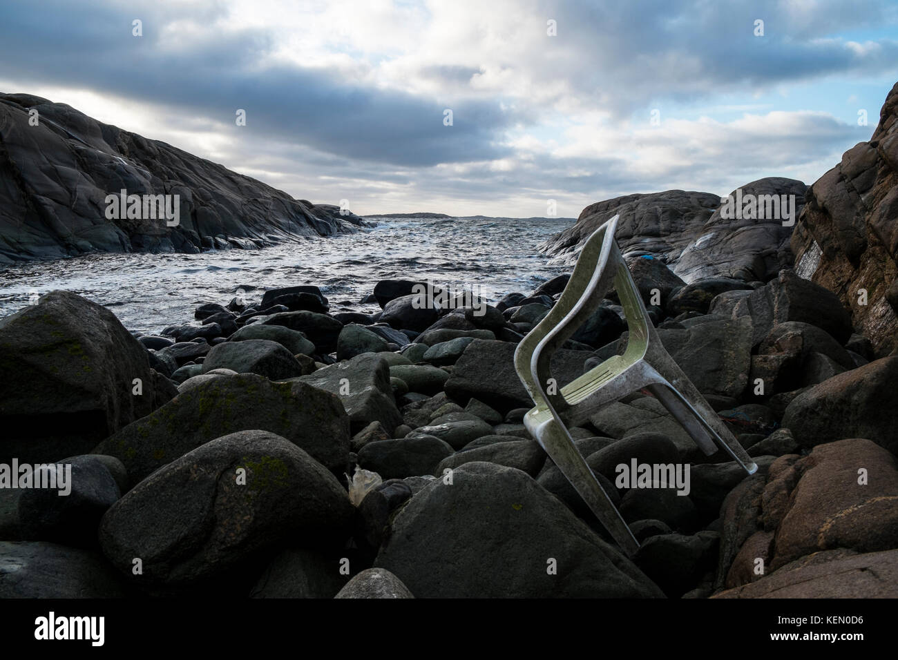 An old plastic chair lying on a rocky shore - Stock Image